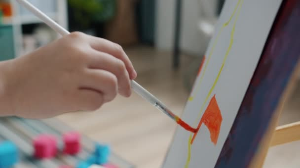 Close-up of kids little hand painting picture with brush and watercolors enjoying art at home
