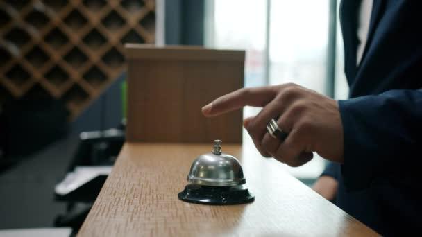 Großaufnahme der klingelnden männlichen Hände klingelt im Hotel und nimmt der Empfangsdame die Schlüsselkarte ab