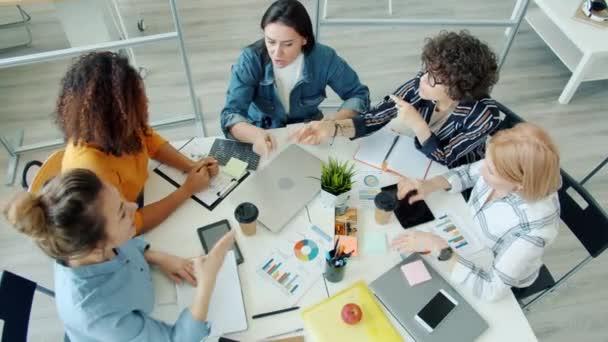 Vysoký úhel pohledu na ženy různé skupiny brainstorming mluvení a gesta u stolu v úřadu