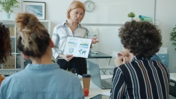 Starší podnikatelka, která prezentuje pro skupinu zaměstnanců mluvící ukazující na graf