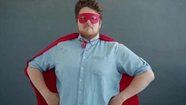 Portrét muže v super hrdina kostým červená pláštěnka a maska na šedém pozadí