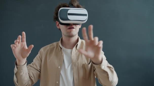 Portrait eines Mannes mit Augmented-Reality-Brille, der Hände auf grauem Hintergrund bewegt und Syberspace-Erfahrung genießt