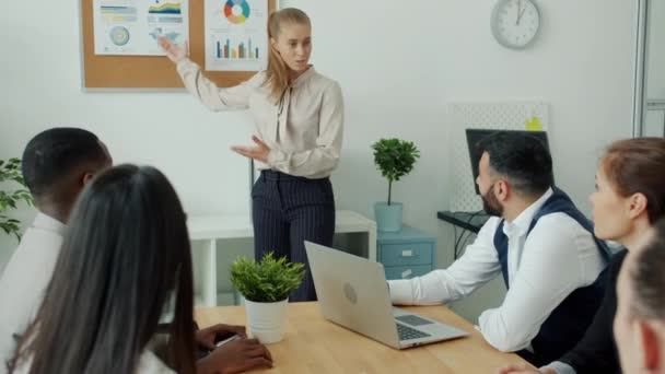 Happy blond woman speaking to colleagues in meeting then dancing enjoying work results
