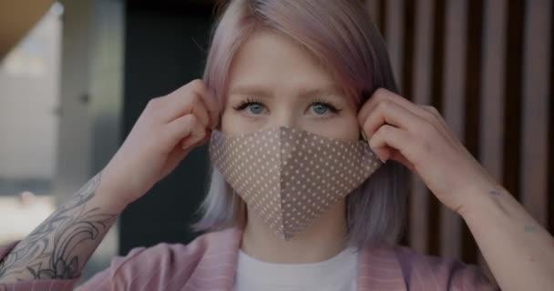 Nahaufnahme der Zeitlupe einer jungen Frau, die ihre Gesichtsmaske abnimmt und lächelt