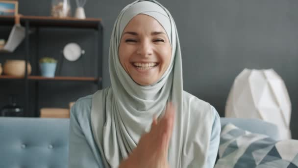 POV of cheerful muslimah chatting on video call enjoying friendly conversation indoors at home
