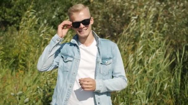 Slow motion portrait of joyful blond man standing against natural bakcground smiling