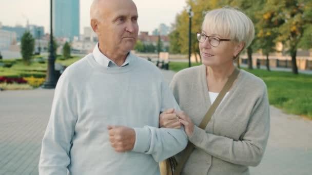 Slow motion of cheerful couple of senior people walking in city talking enjoying summer day