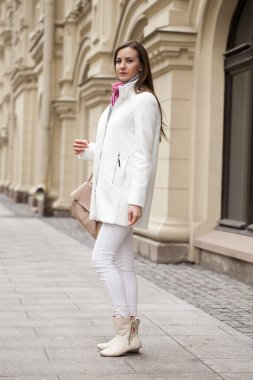 Young beautiful woman in white coat on the background of spring