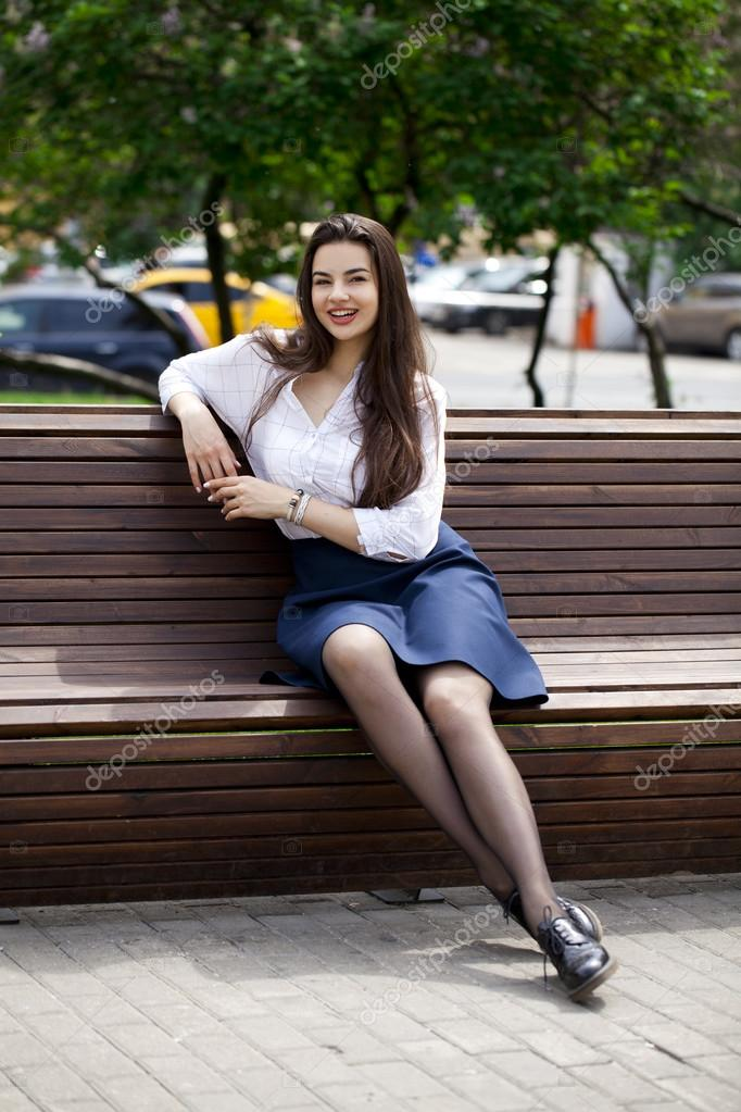 Belle fille brune assise sur un banc dans un parc
