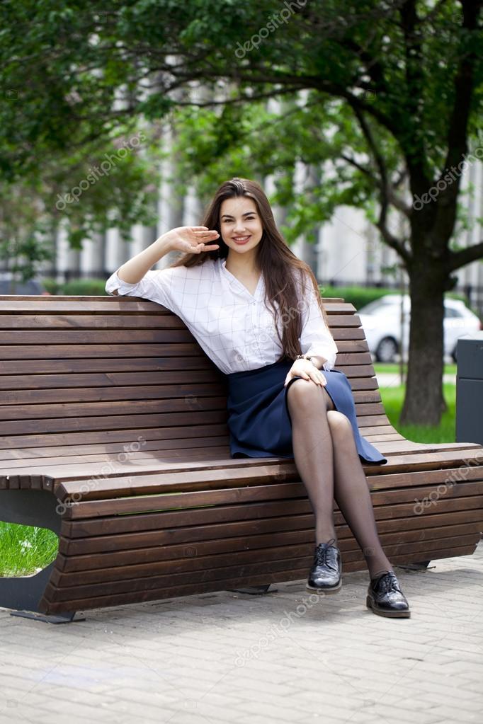 Jeune Belle Fille Saluant, Assis Sur Un Banc Dans Le Parc