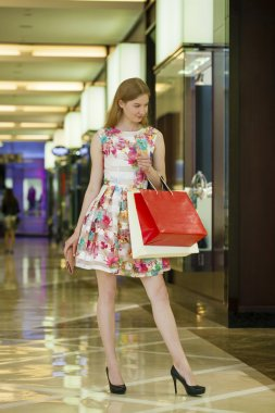 Young blonde woman with some shopping bags in the mall