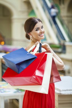 Happy brunette woman with some red shopping bag