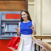 Photo Happy brunette woman withdrawing money from credit card at ATM