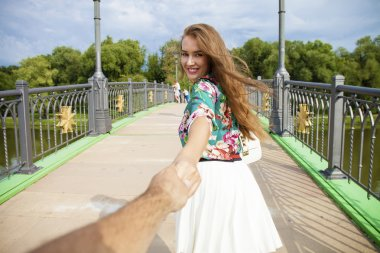 Follow me, Beautiful young woman holds the hand of a man