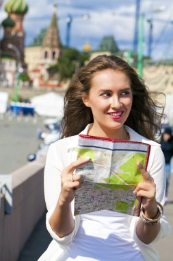 Young beautiful girl holding a tourist map of Moscow