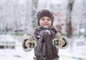Fotografia Bambina felice sullo sfondo di un parco di inverno