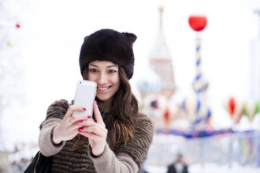 Young beautiful woman tourist taking pictures on mobile phone