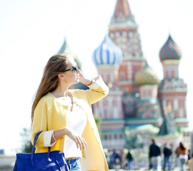 Young beautiful happy woman calling by phone in Moscow