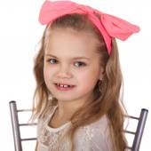 Fotografie Portrait of a little girl with a red bow on her head