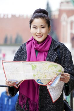 Young beautiful asian girl holding a tourist map of Moscow