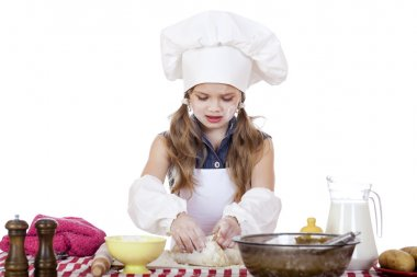 Little girl in a white apron and chefs hat knead the dough in th