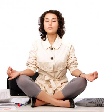 Attractive white collar worker meditating in office