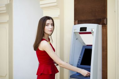 Brunette young lady using an automated teller machine . Woman withdrawing money or checking account balance stock vector