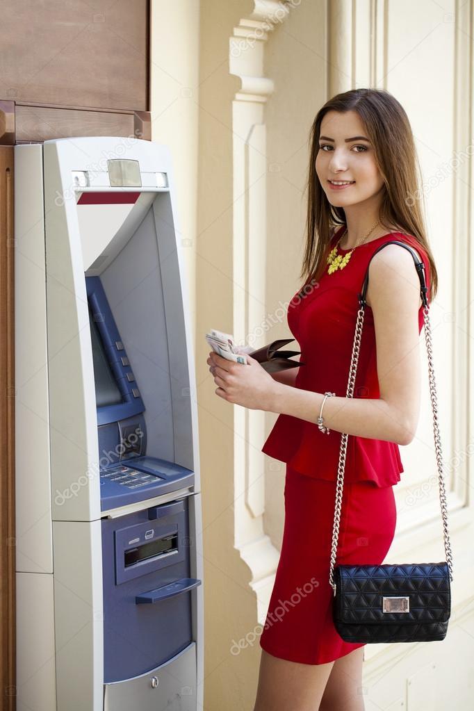 jeune femme en robe rouge l 39 aide d 39 un distributeur automatique photographie arkusha 70316605. Black Bedroom Furniture Sets. Home Design Ideas