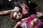 Pár zakrvácený muž a žena ležící na zemi