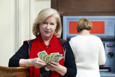 Mature blonde woman counting money near ATM