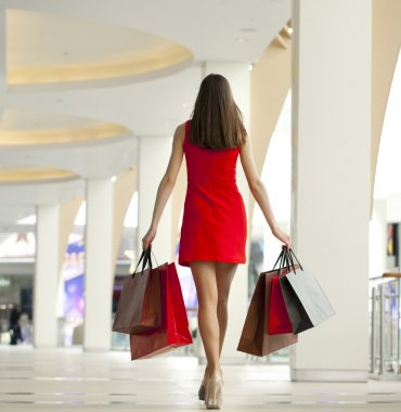 Beautiful young woman holding shopping bags walking in the shop