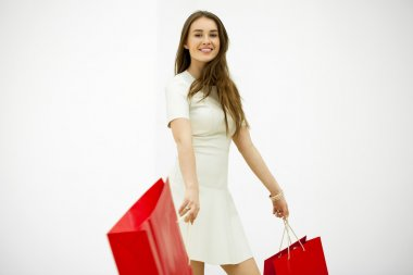 Smiling young blonde girl with colorful shopping bags in white d