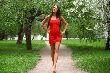 Happy young woman in red dress against the background spring flo