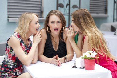 Three beautiful girlfriends gossiping woman sitting at a table i