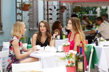 Three happy girlfriends woman sitting at a table in the summer c