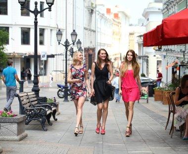 Three beautiful young women girlfriends walk on a summer street