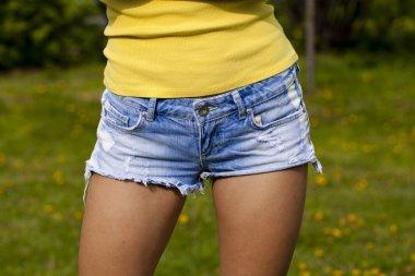Beautiful woman body in denim jeans on summer street