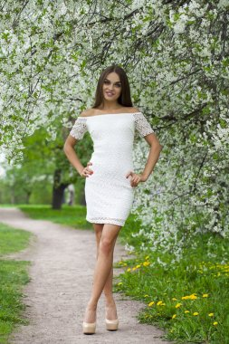 Happy young woman in white dress walking in spring park