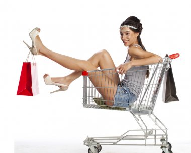 Young beautiful brunette girl sits in an empty shopping cart wit
