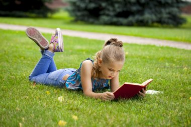 Adorable cute little girl reading book outside on grass