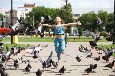 Young happy girl runs through a flock of pigeons on the square