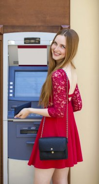Blonde lady using an automated teller machine