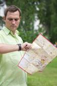 Young male tourist with map in hand looking at wristwatch