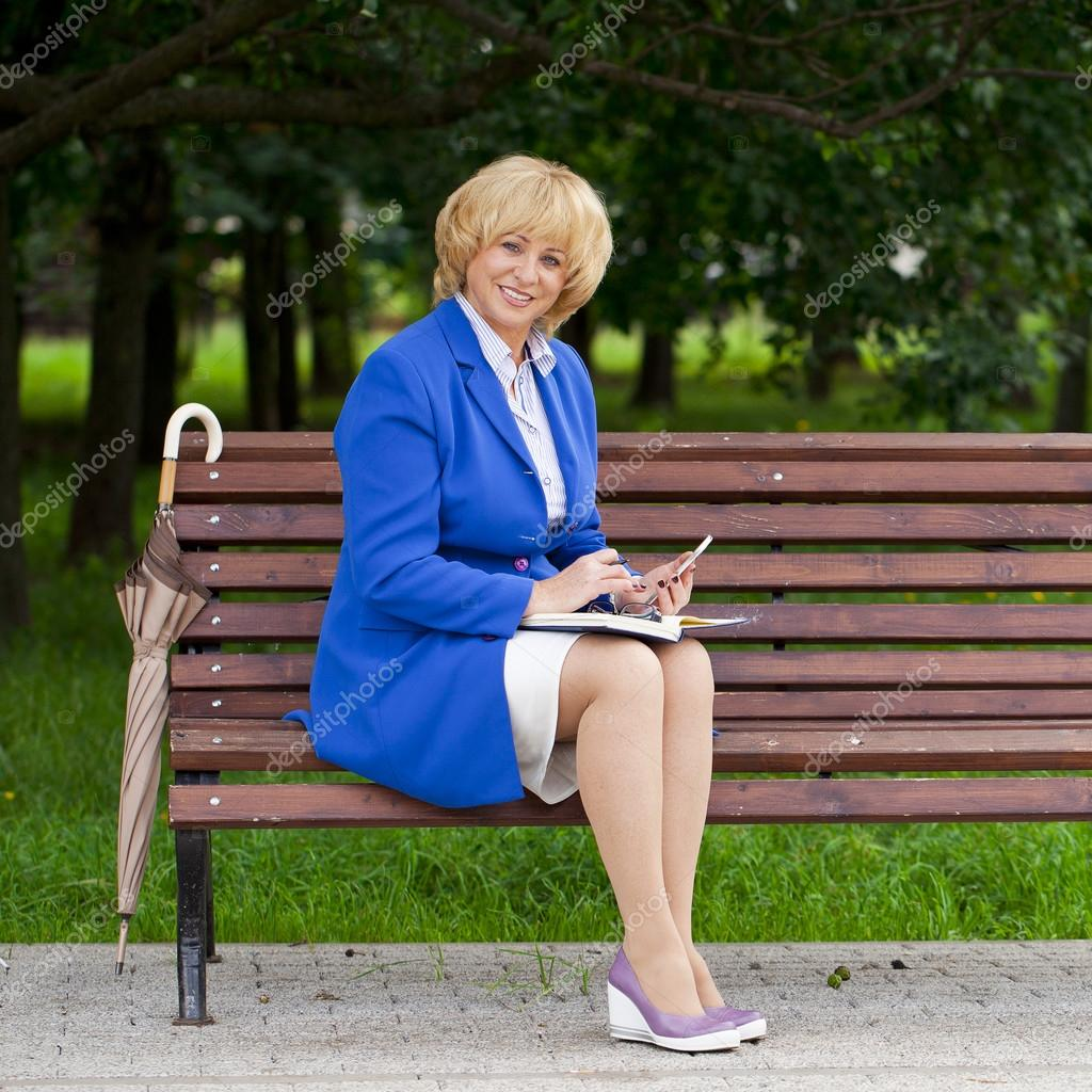 mature business woman in a jacket with diary sitting on a bench