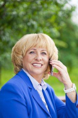 Portrait of an elderly beautiful woman talking on a cell phone