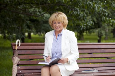 Portrait of serene mature woman in the summer park