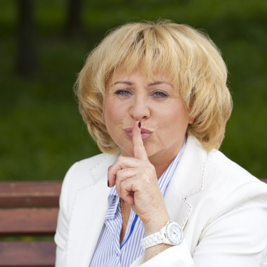Portrait of old blonde woman with finger on lips