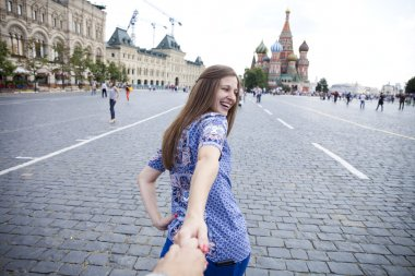 Young happy girl pulls the guys hand on the Red Square in Moscow