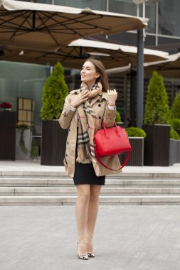 Young beautiful woman in beige short coat posing outdoors in spr