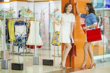 Two young beautiful girls standing at the storefront